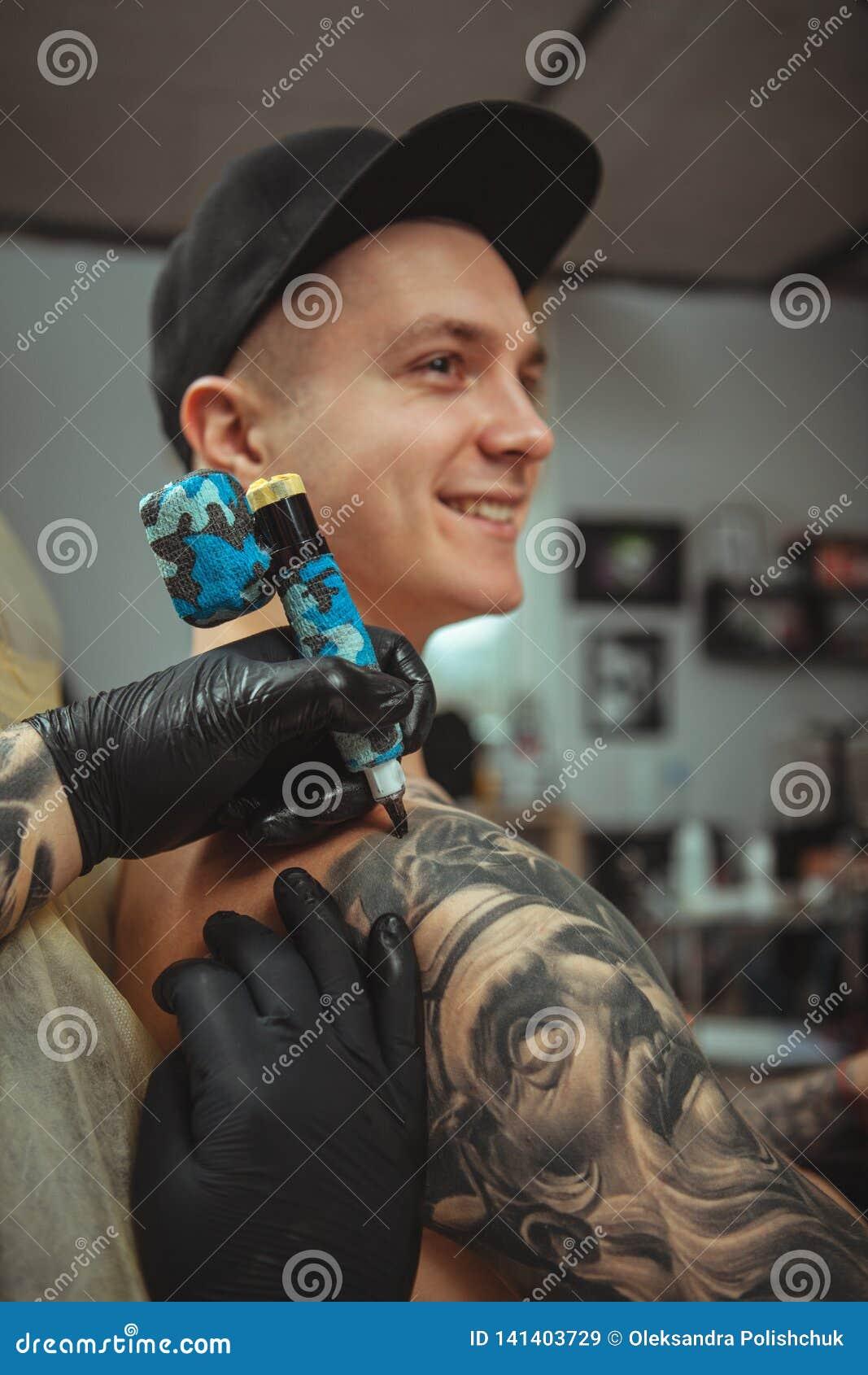 Gut aussehender Mann, der eine Tätowierung am alternativen Kunststudio erhält
