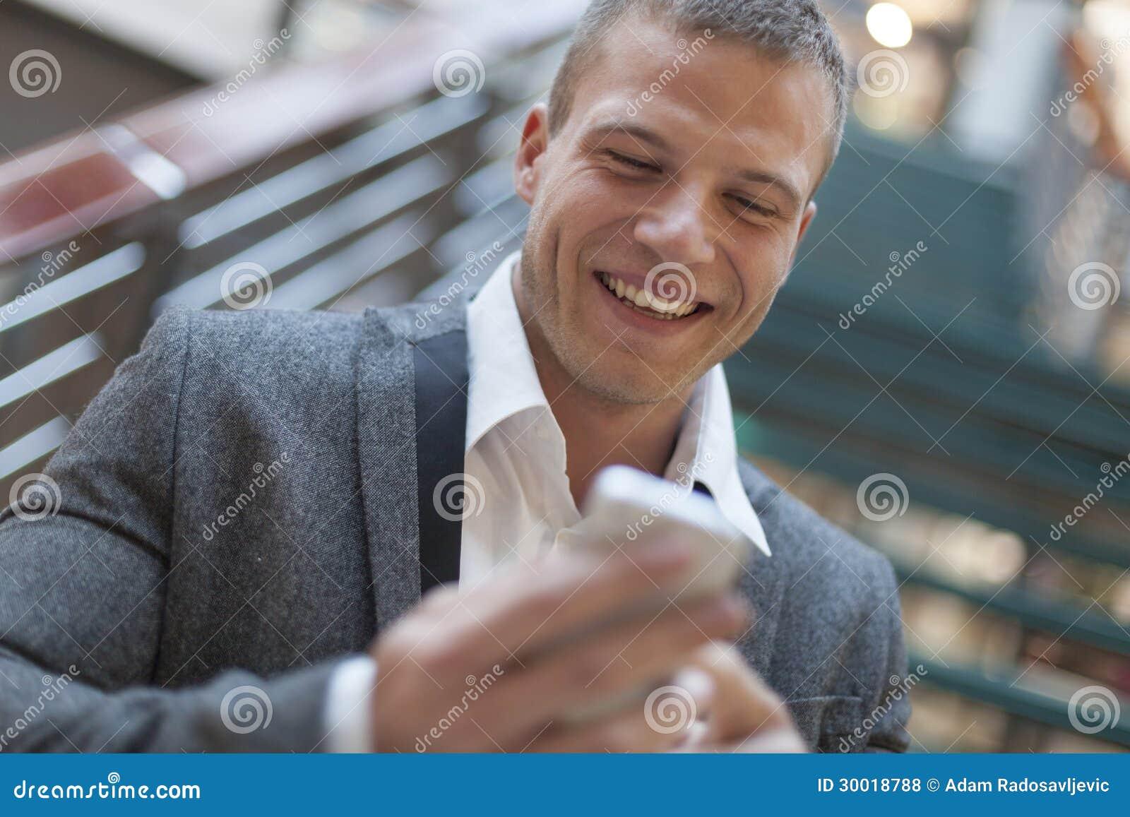 Gute Nachrichten! Männer, die sms auf smartphone im Geschäftsgebäude lesen