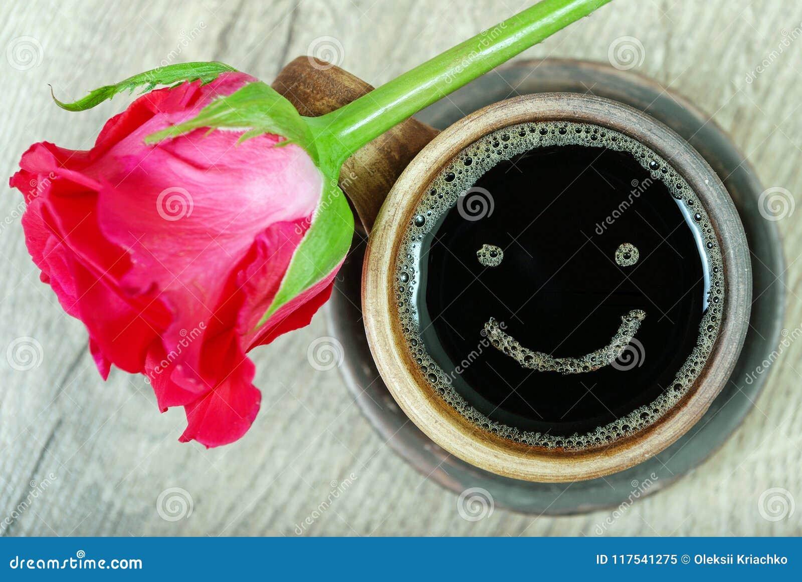 Guten Morgen ein Tasse Kaffee und eine rote Rose auf einem Holztisch Lächeln eines glücklichen Tages