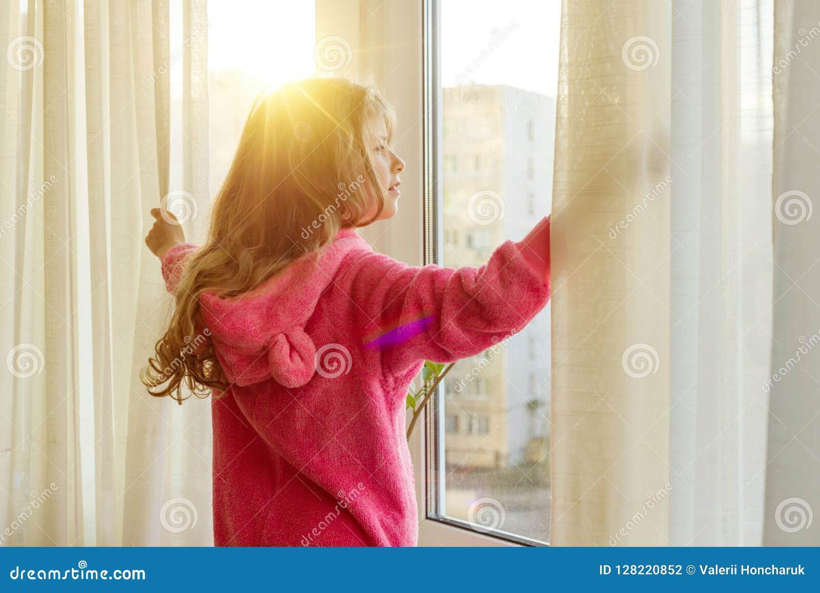 Guten Morgen Mädchenkind in den Pyjamas öffnet Vorhänge und Blicke heraus das Fenster