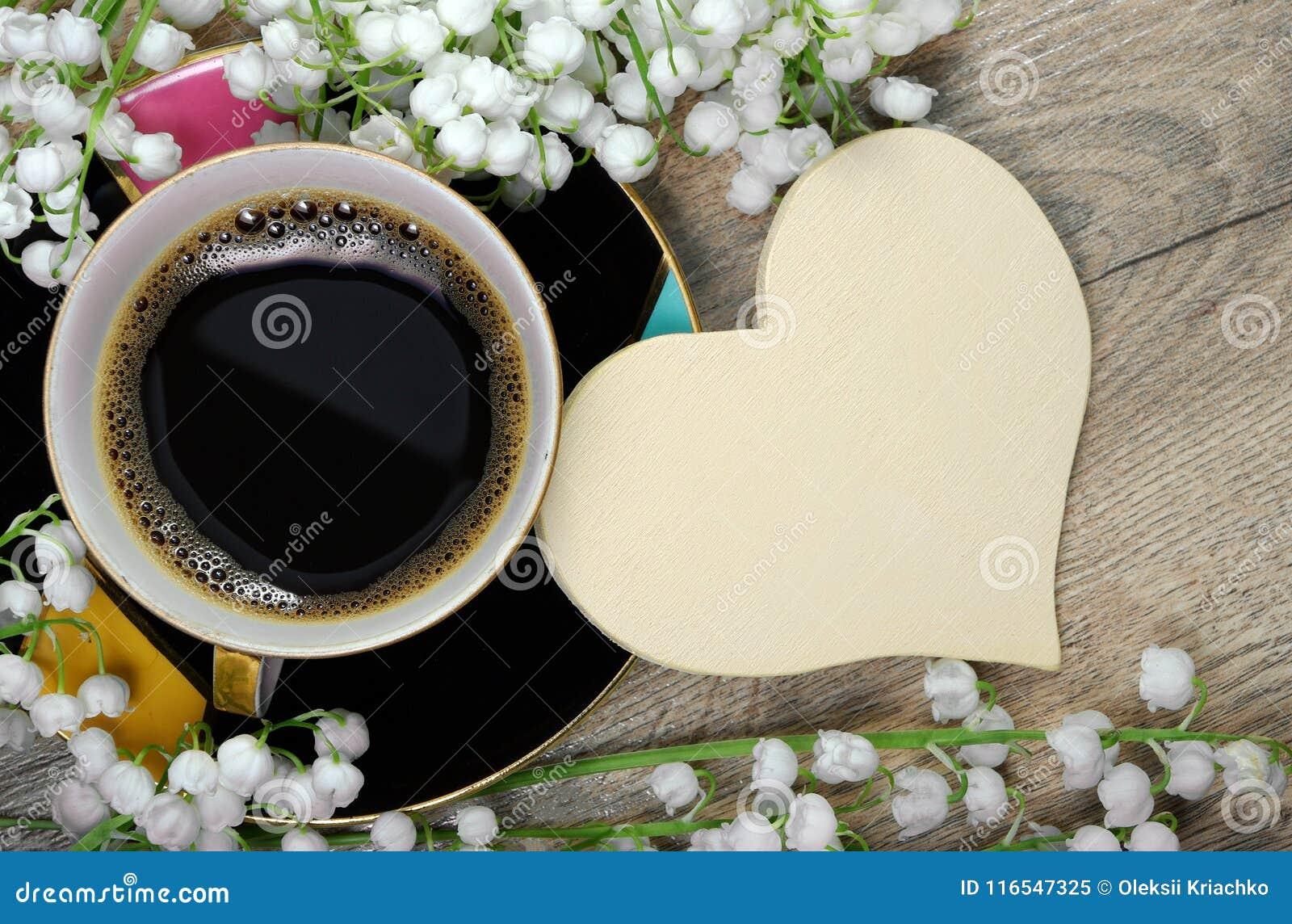 Guten Morgen Morgenkaffee und -Maiglöckchen blühen auf einem Holztisch