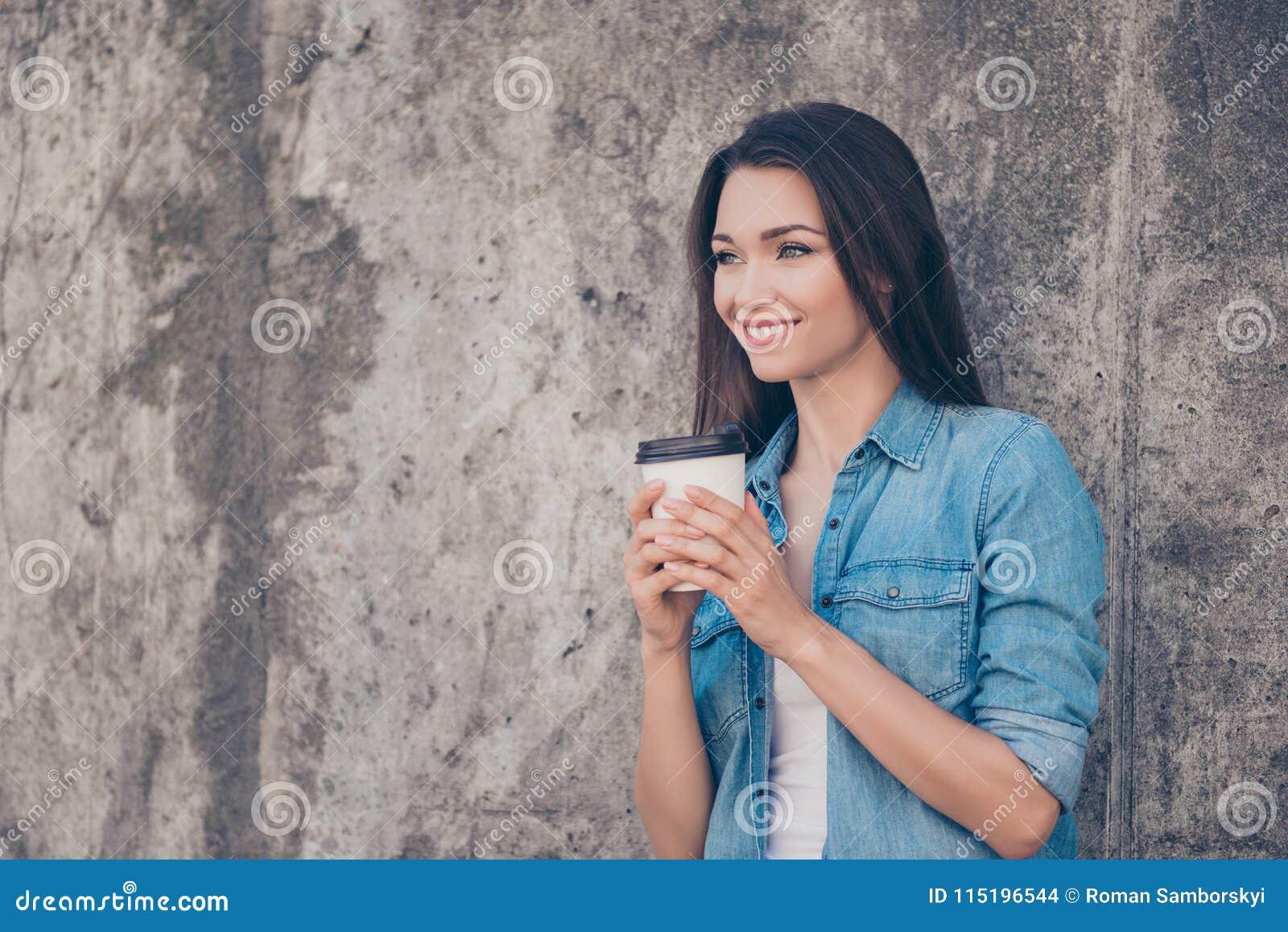 Guten Morgen! Nette recht junge ruhige Brunettedame trinkt heißen Tee nahe Betonmauer draußen, das Lächeln und trägt gemütliches
