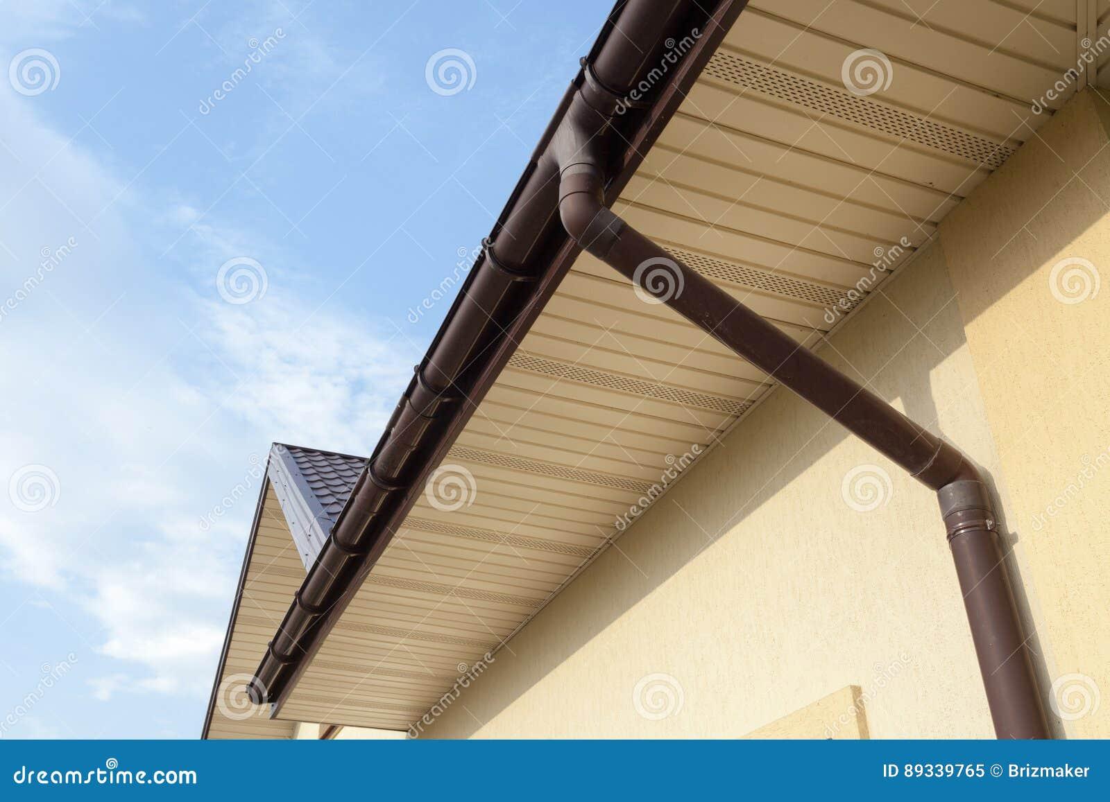Guttering home, calhas, sistema plástico de Guttering, Guttering & tubulação da drenagem exterior contra o céu azul