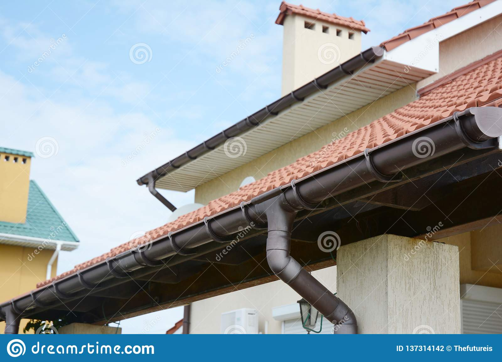 Guttering. Roof gutter pipeline sysem. House rain gutter with holders and downspout pipe