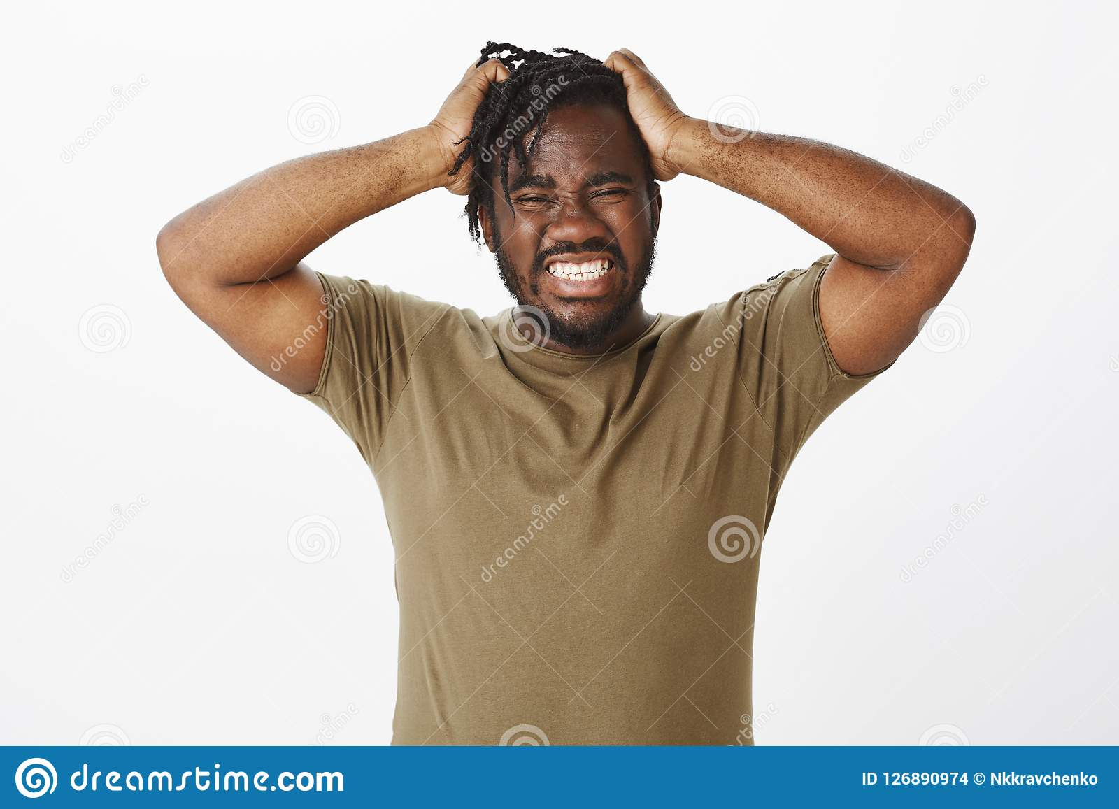 Guy cannot hold negative emotions inside. Depressed desperate african american man in olive t-shirt, holding hands on
