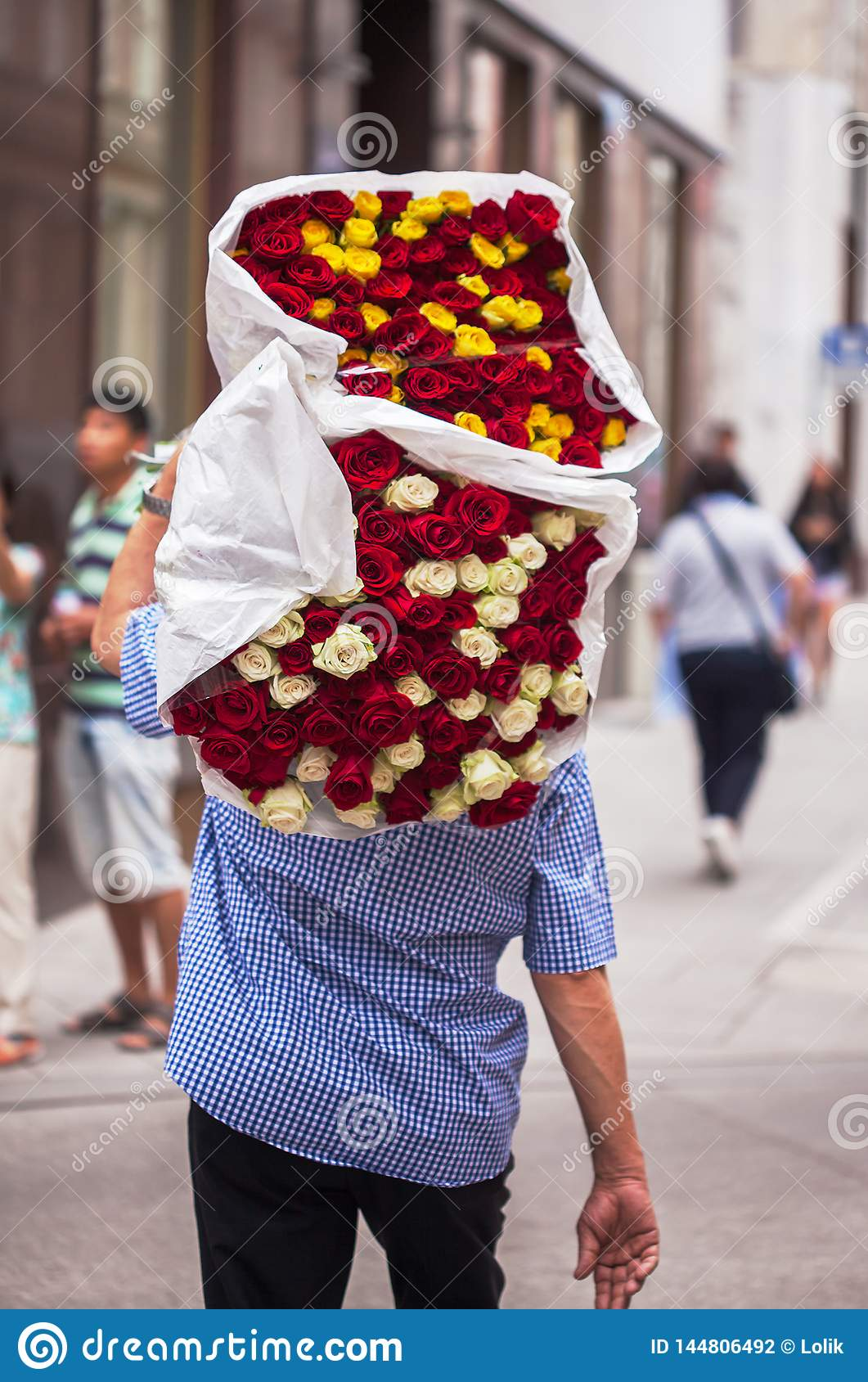 The guy carries a big bouquet with red, white and yellow roses