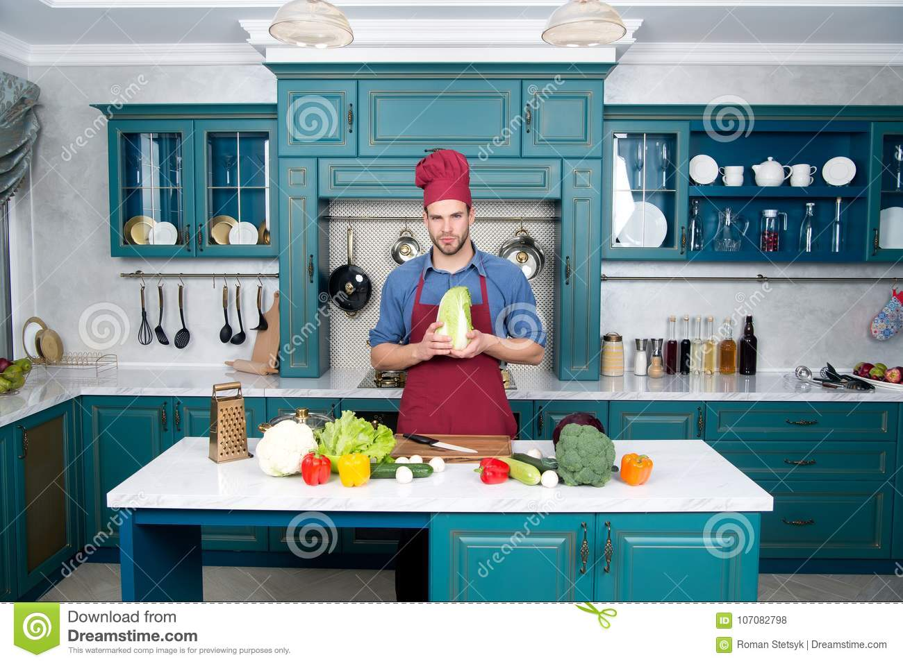 Guy In Chef Hat, Apron Hold Chinese Cabbage In Kitchen Stock Photo ...