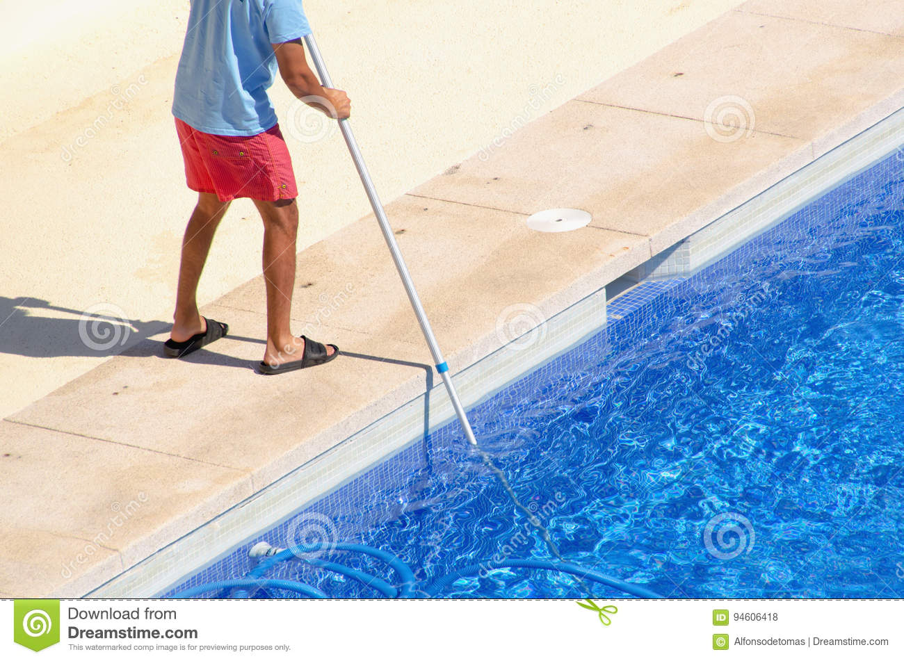 Swimming Pool Cleaning Head : Guy cleaning the swimming pool with a vacuum head stock