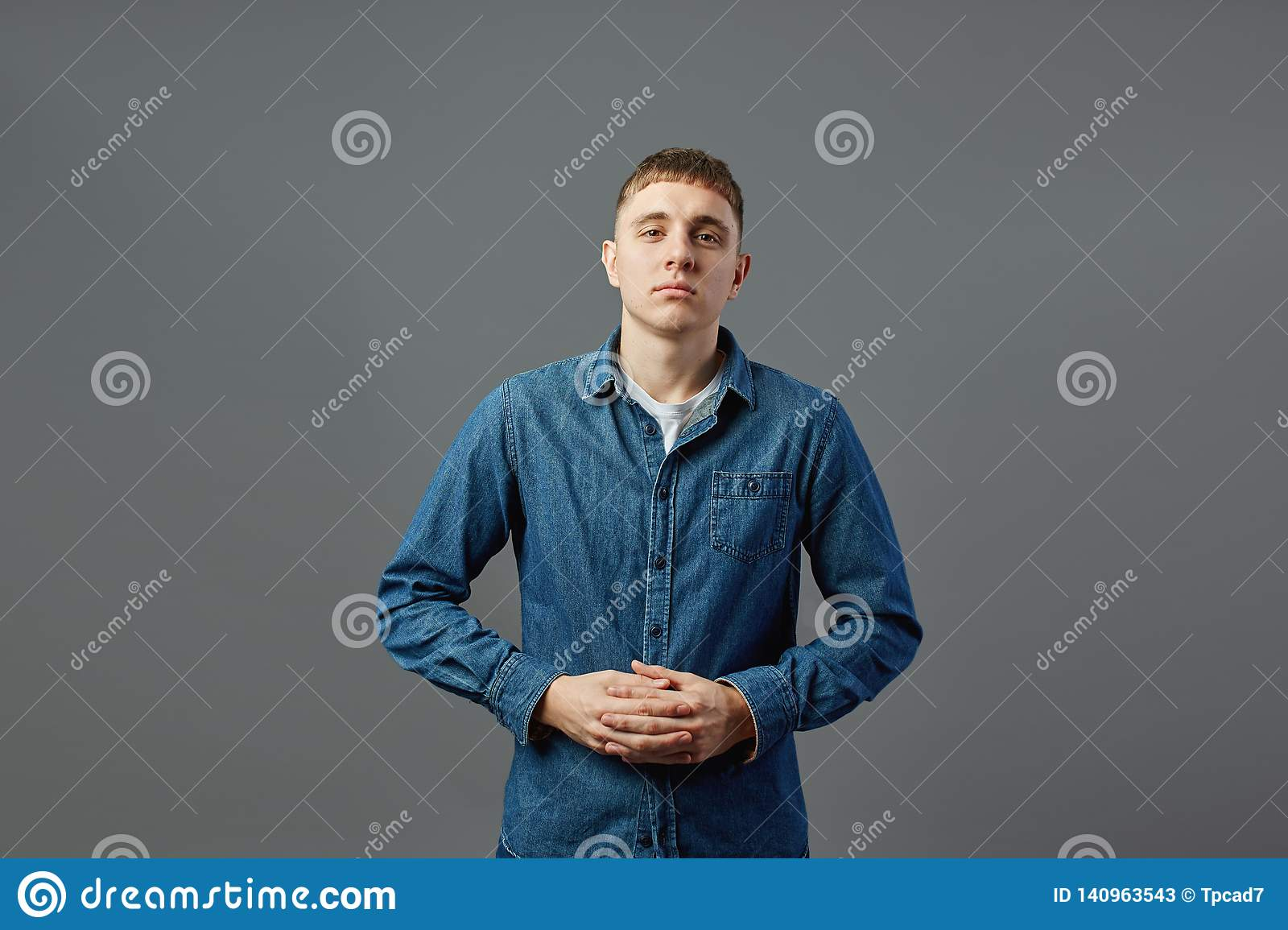 Guy dressed in a white t-shirt, jeans and jeans shirt standing with his arms folded in the studio on the gray background
