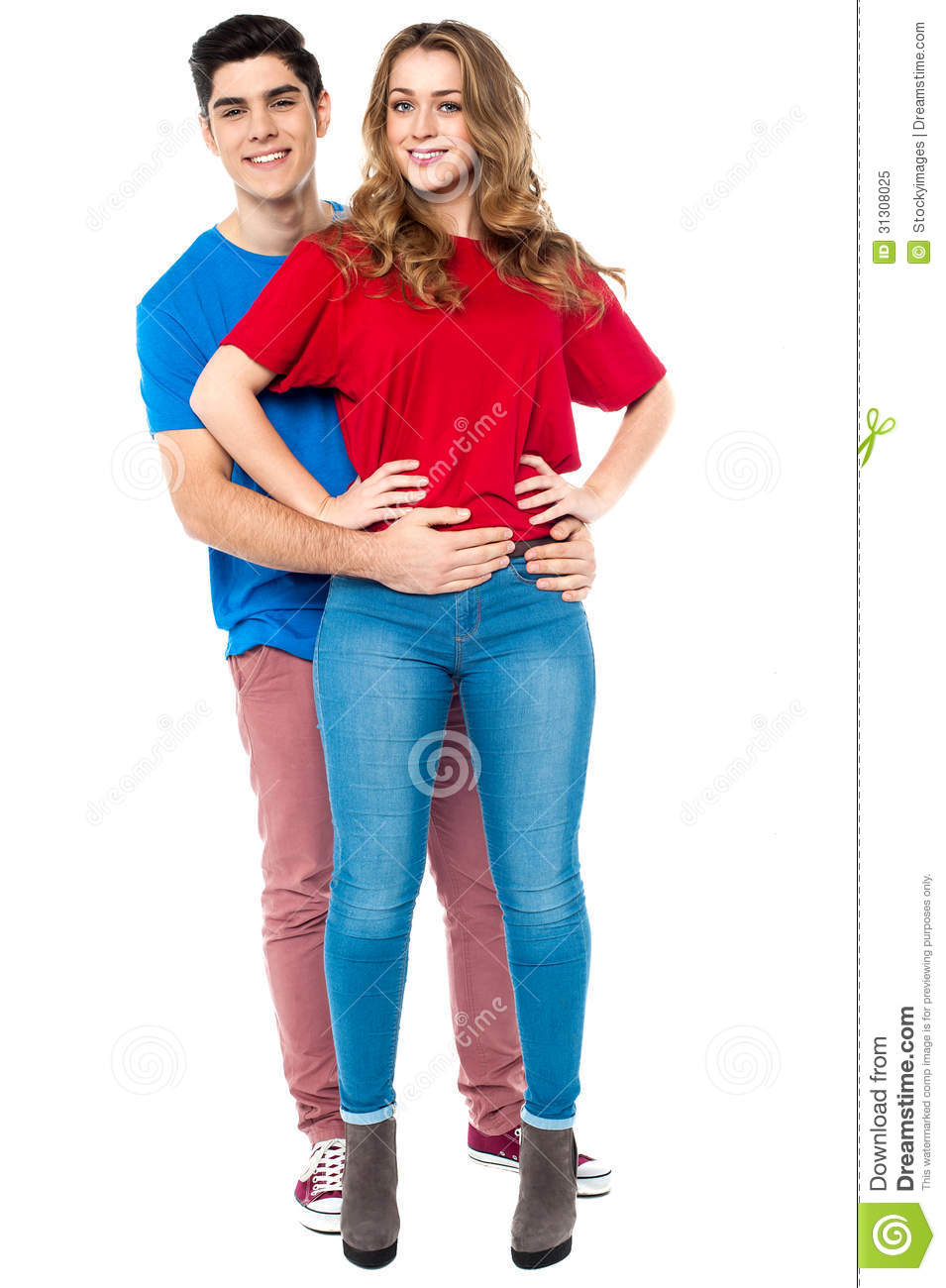 Guy embracing his girl from behind, arms around