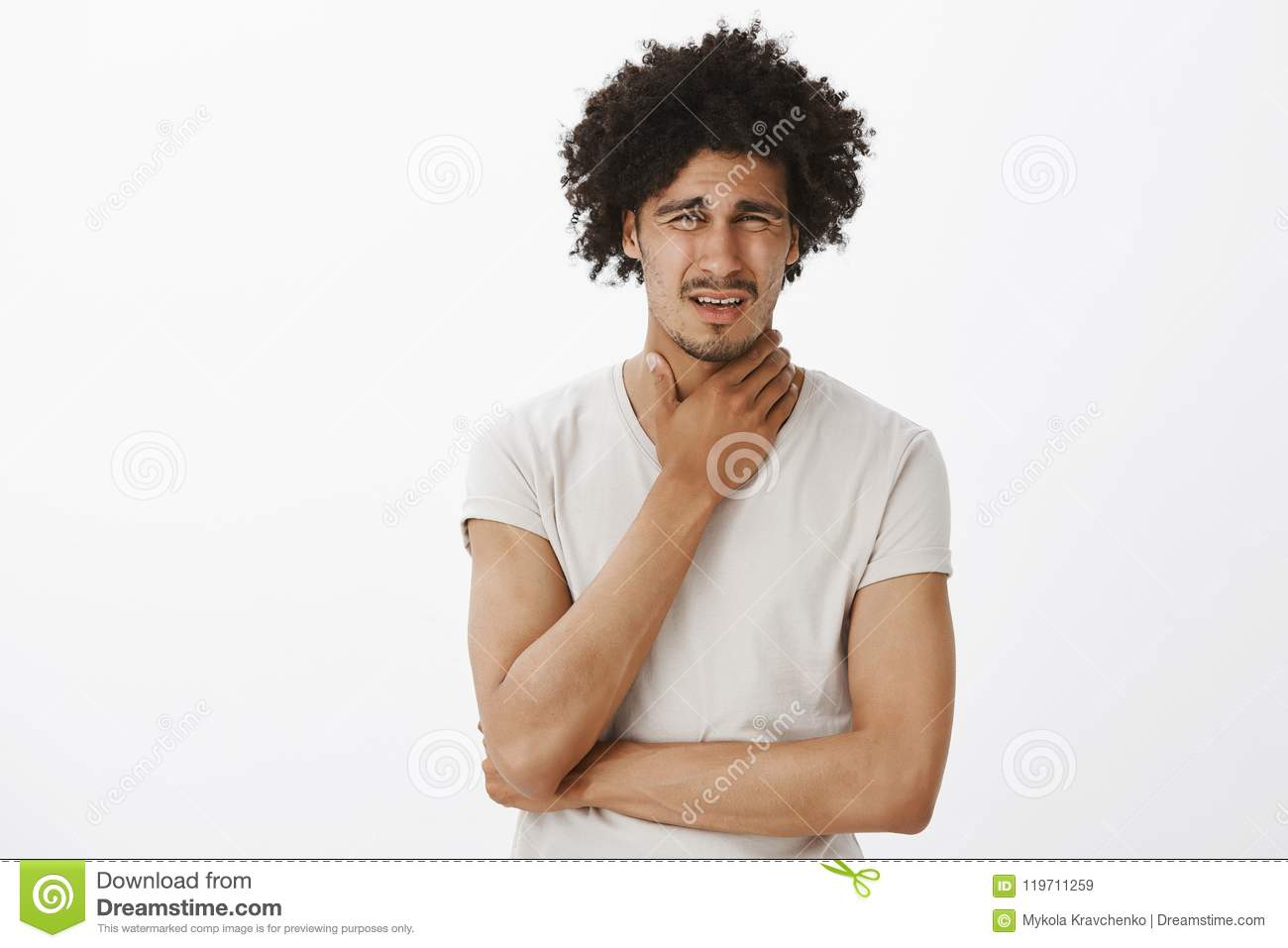 Guy feeling pain in throat, catching cold, frowning and grimacing from painful feeling, rubbing neck, standing intense