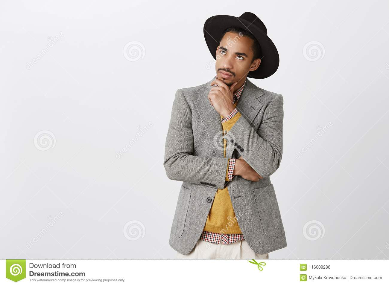 Guy focused on thoughts, making hard decision. Concentrated serious dark-skinned male freelancer in black hat and