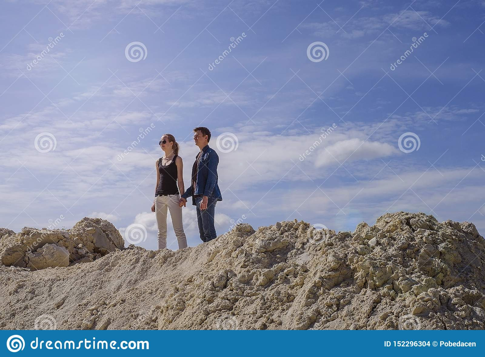 The guy with the girl against the blue sky at the top of the mountain