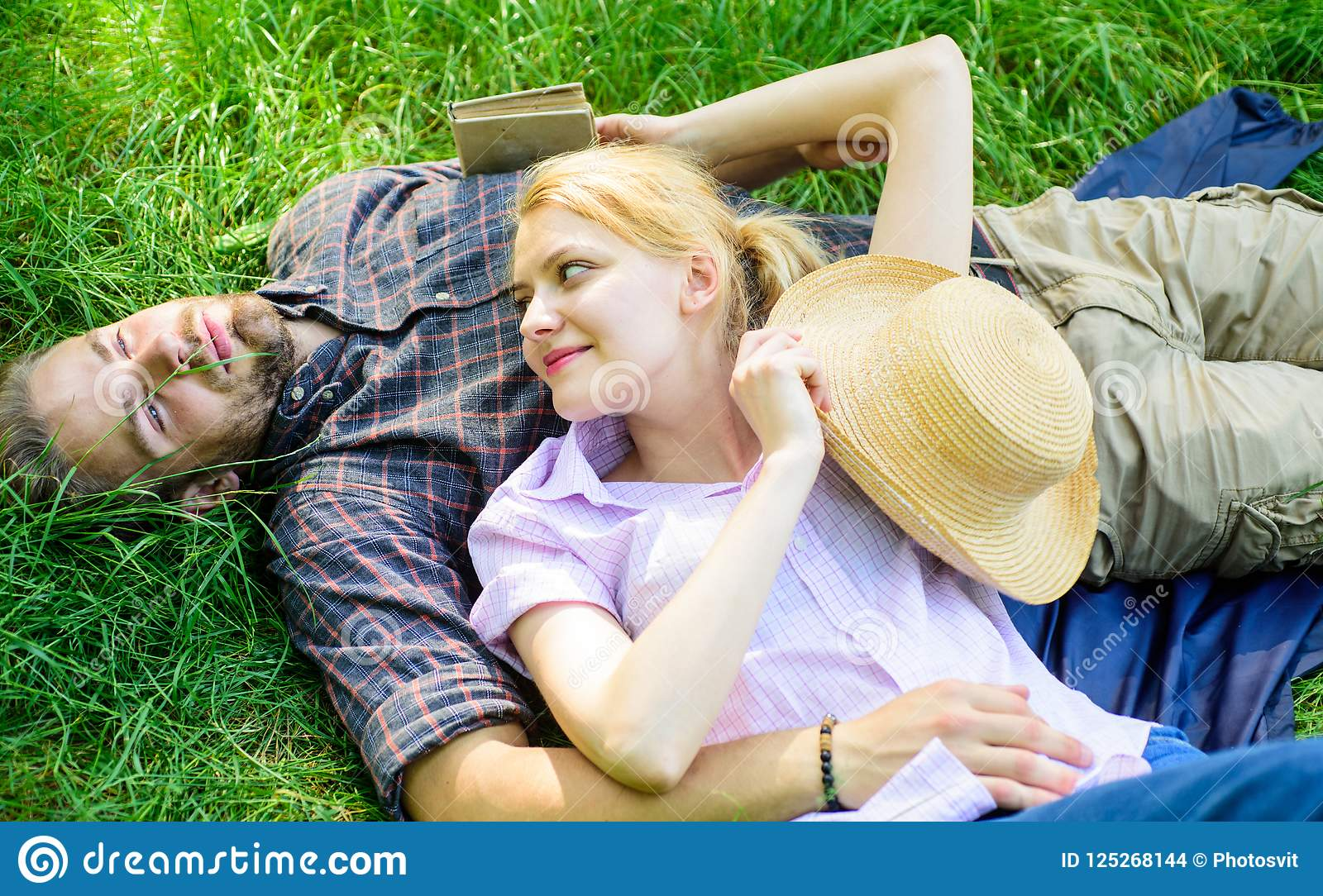 Guy and girl dreamy relaxed enjoy tranquility nature. Couple in love relaxing outdoors. Man unshaven and girl relax on