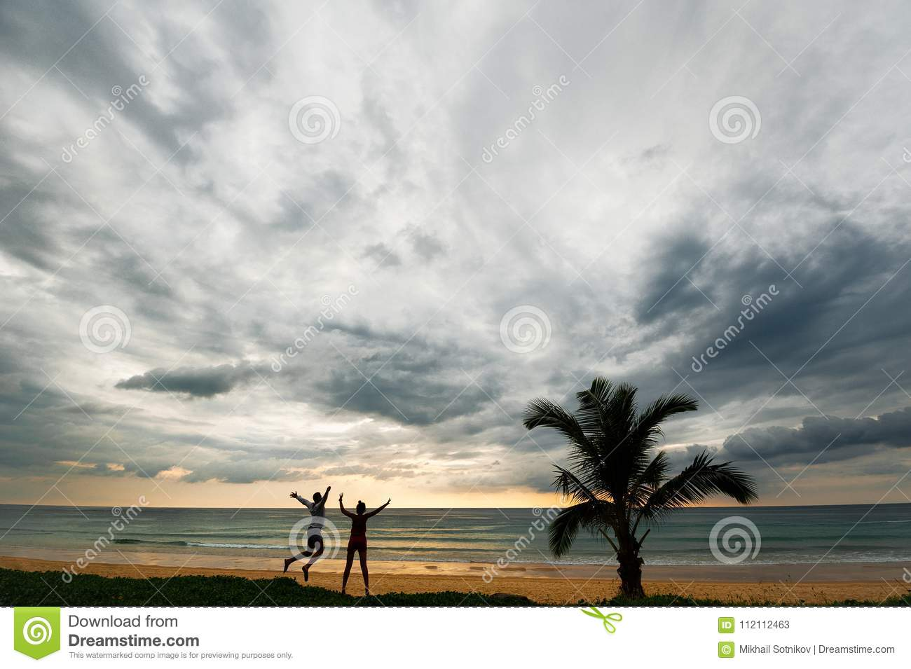 Guy and girl having fun at sunset by the sea