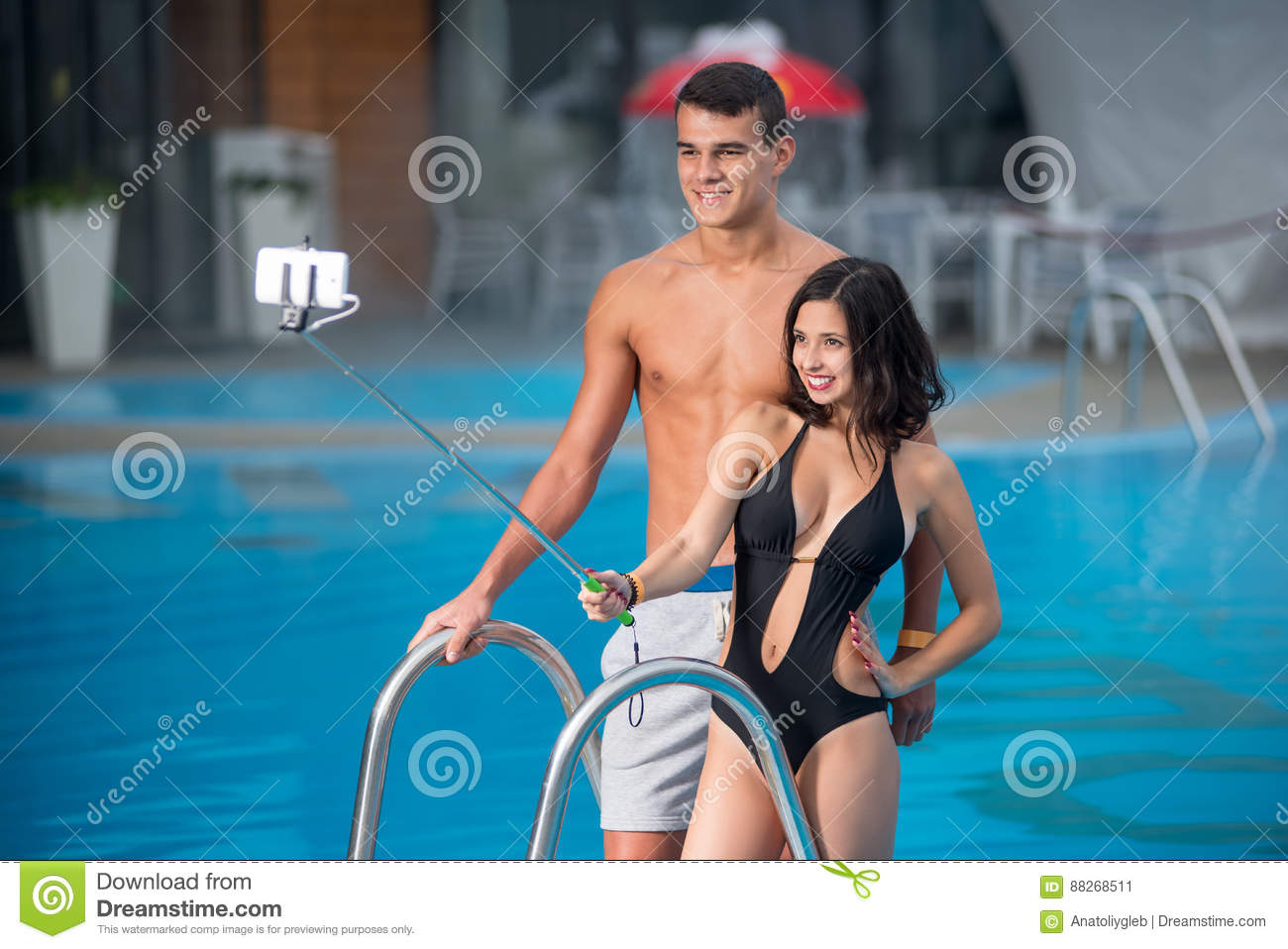 Guy And Girl Posing Against The Swimming Pool With Perfect