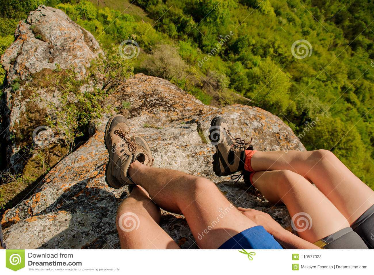 Guy and a girl in sneakers sit on a rocky mountain, dangling their legs down