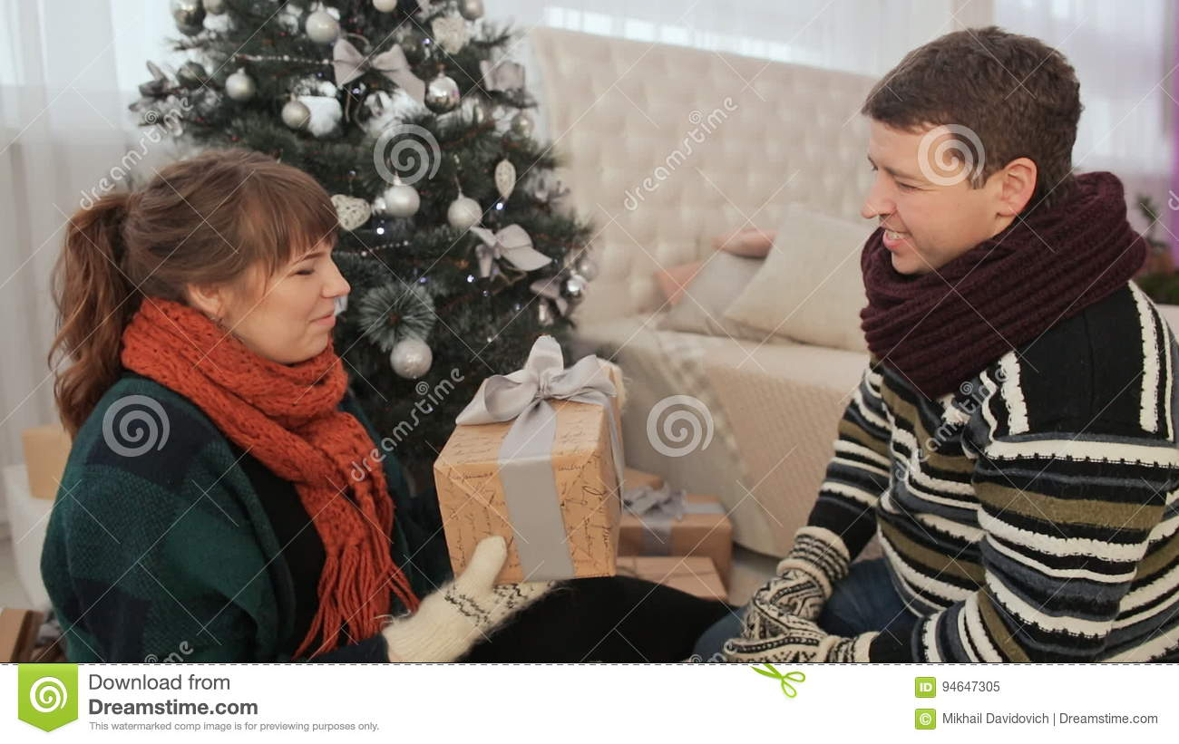 The Guy Gives The Girl Christmas Gifts. The Girl Model Shows Off A Gift To The Viewer. Cozy Homely Atmosphere. Stock Video - Video of present, ...