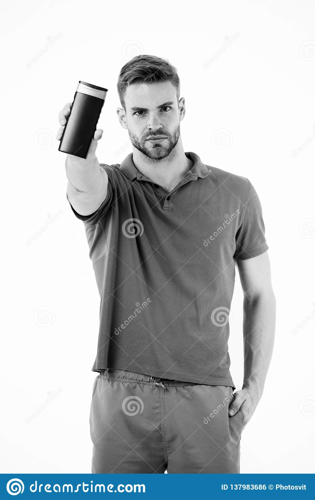 Guy handsome use popular cosmetic or hygienic shampoo product. Man show his favorite shampoo conditioner for hair. Guy