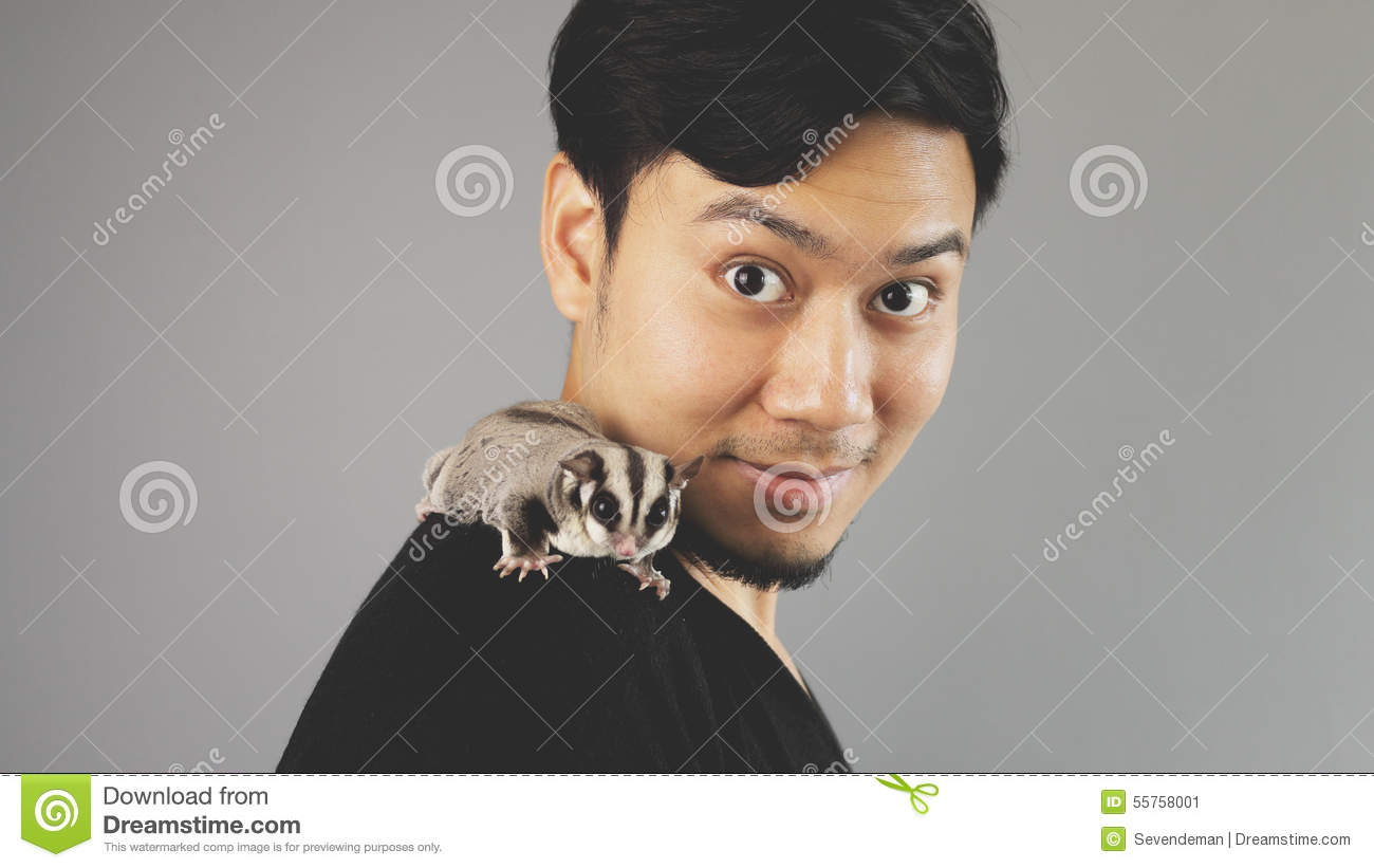 A guy with his exotic pet on his shoulder.