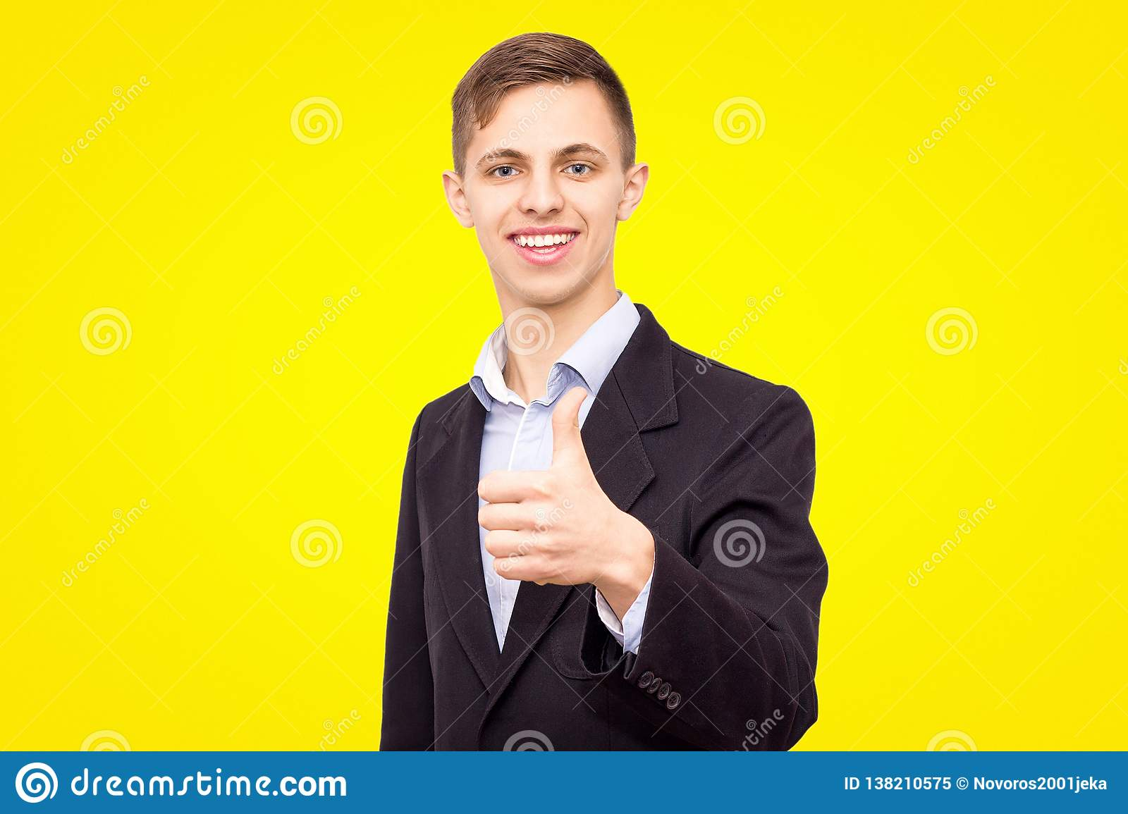 Guy in a jacket and blue shirt shows a finger up isolated on a yellow background