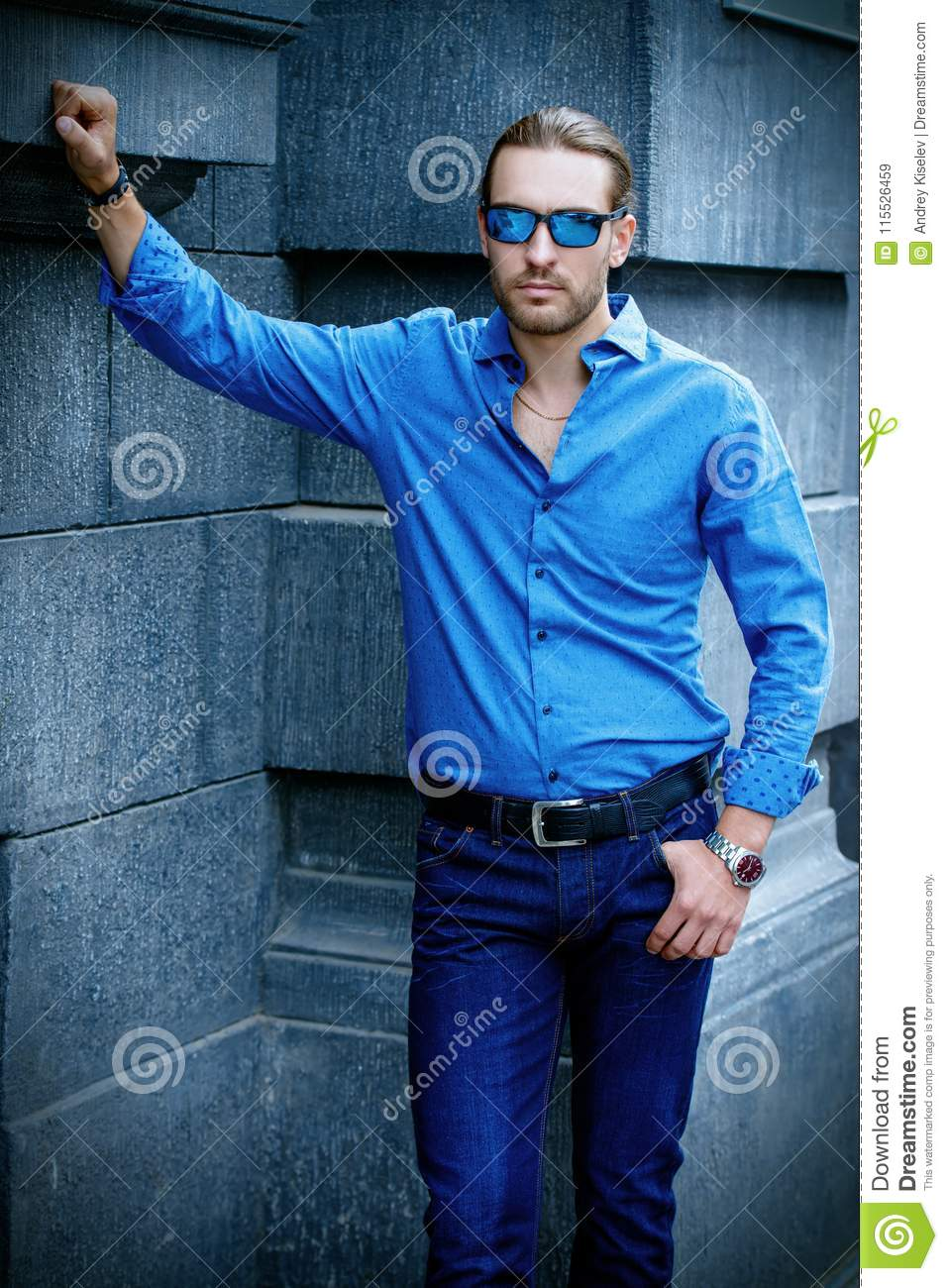 7b618887 Handsome young man in jeans clothes stands on a city street. Men`s fashion.