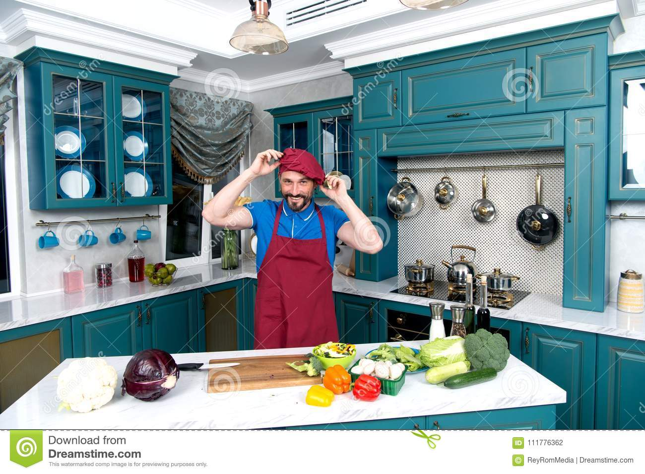 Guy at kitchen dressing apron and hat. Chef wears red uniform. Man dressed on red hat on hand.