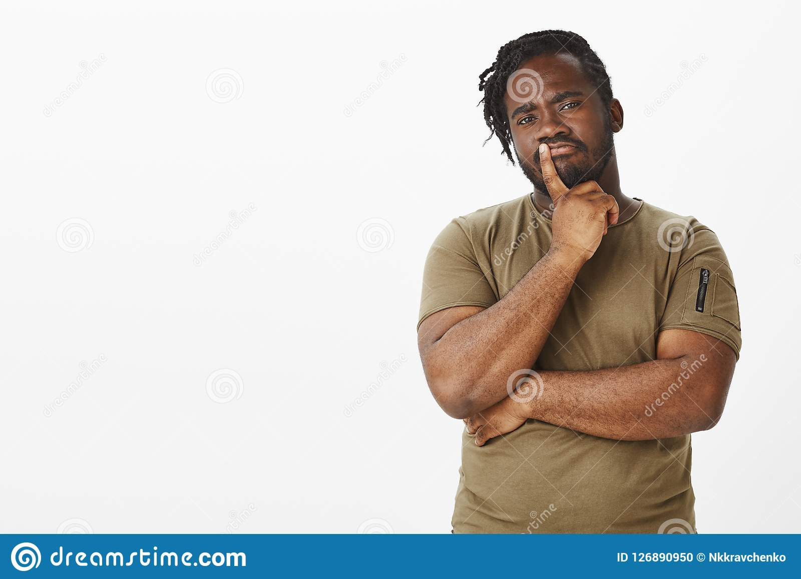 Guy making importrant decision. Portrait of smart thoughtful african boyfriend in military t-shirt, frowning and holding