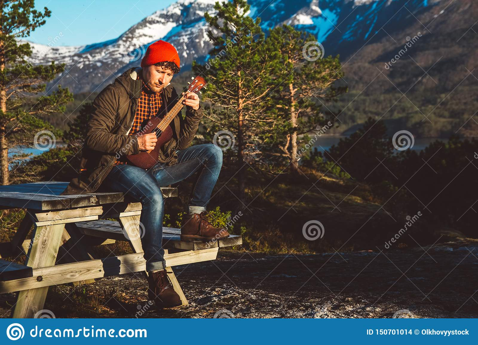 Guy playing guitar sitting on a wooden table against the background of mountains, forests and lakes, wear a shirt and a
