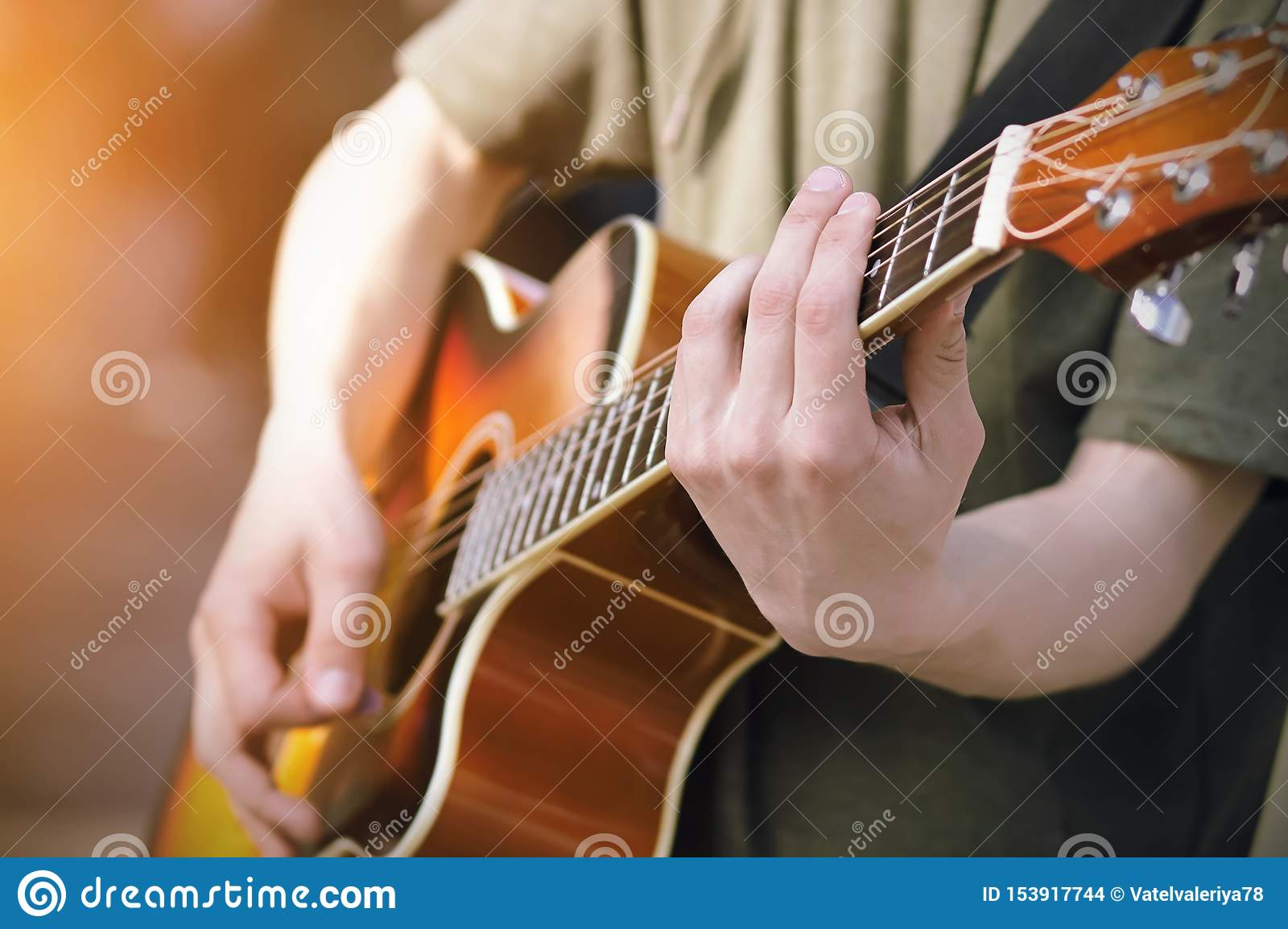 The guy plays an orange acoustic six-string guitar