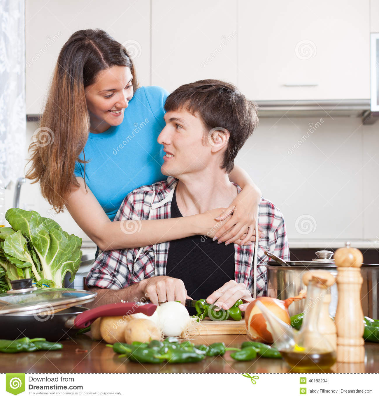 Guy And Pretty Girl Cooking In Domestic Kitchen Stock