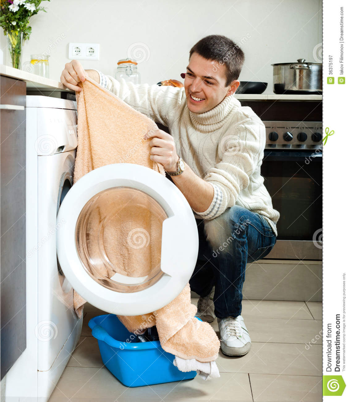 Clothes Washing Machine ~ Guy putting clothes in to washing machine stock image