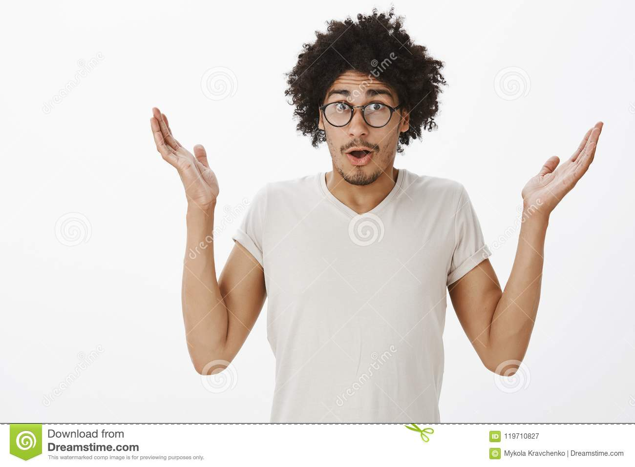 Guy saying sorry forgetting about buying milk, shrugging and spreading palms high, standing with confused and questioned