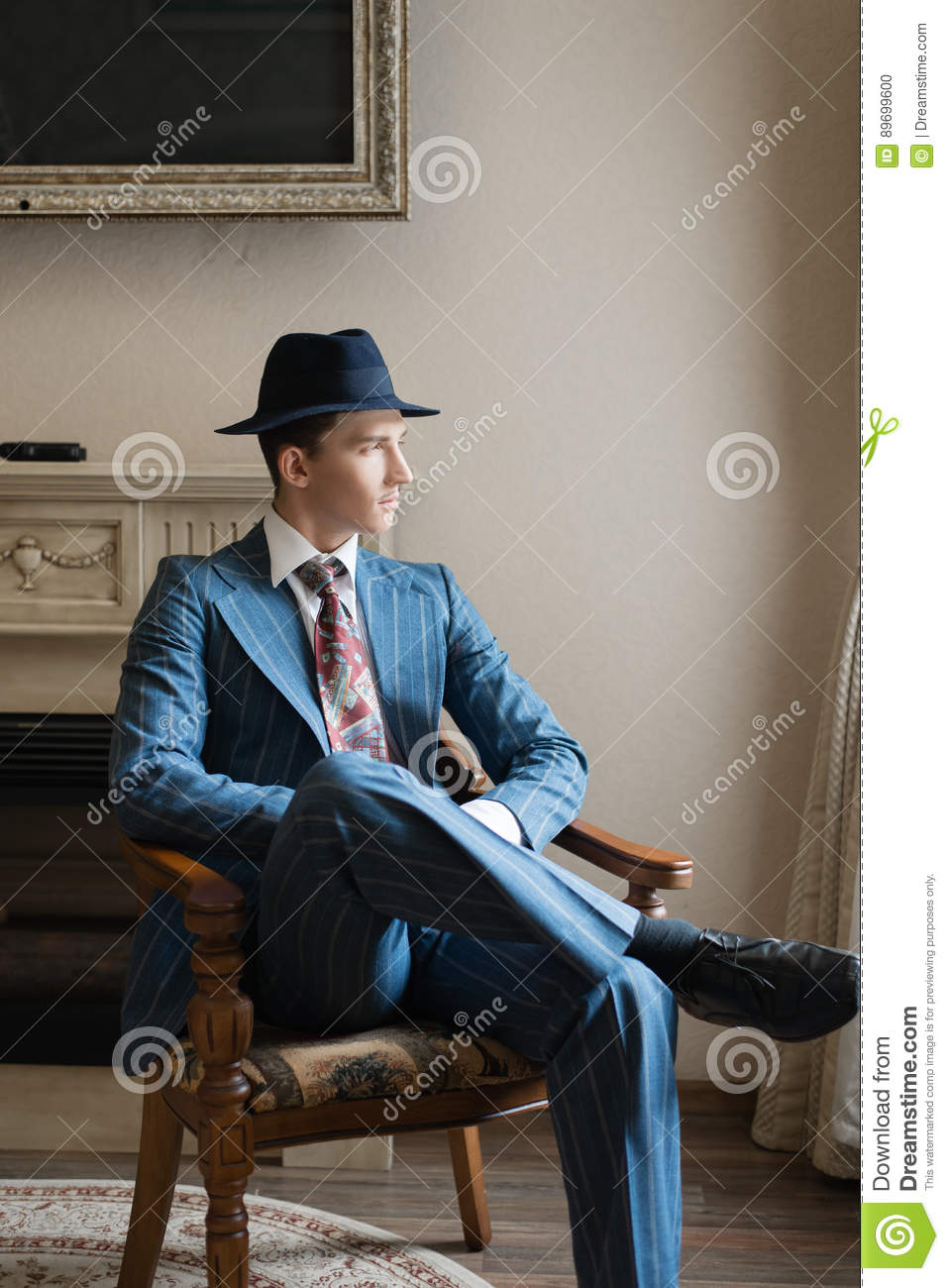 Young Rich Businessman Sitting In Armchair Stock Photo