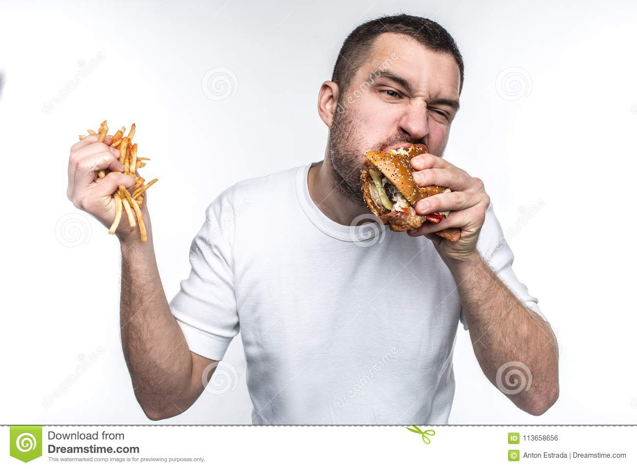 This guy is very delight of junk food. He is biting a big piece of burger and holding a full hand of french fries