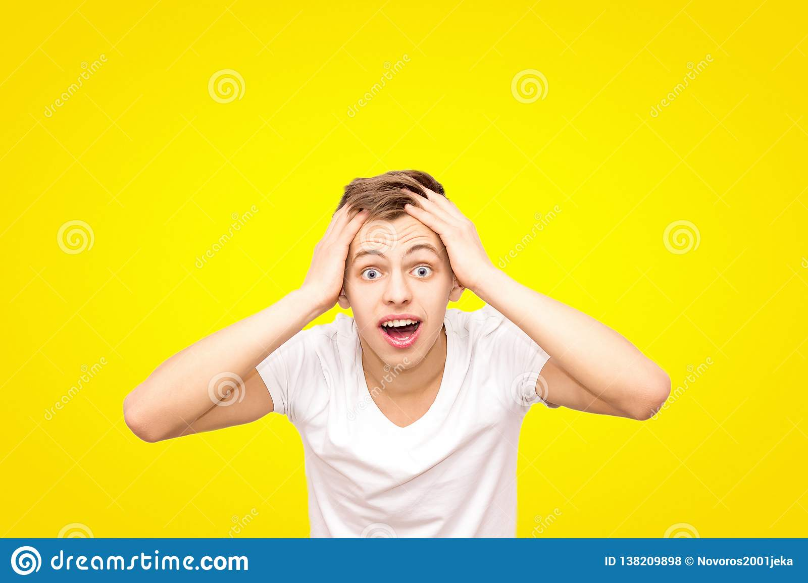 Guy in white in a white T-shirt holding his head, isolated on a yellow background