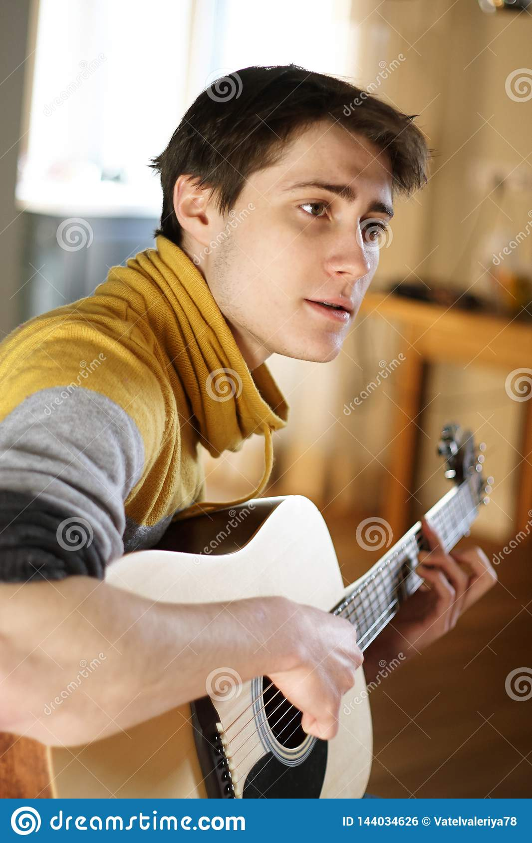 A guy in a yellow sweater sings a song, playing at his guitar