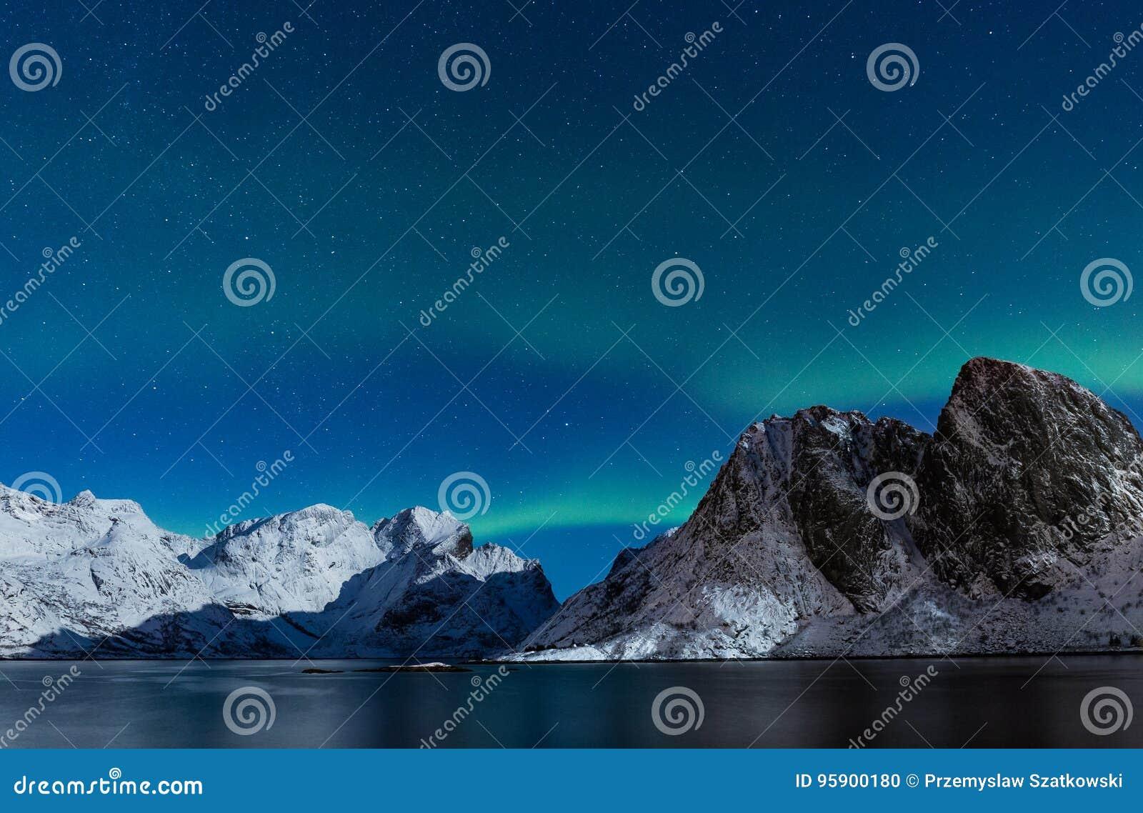 Gwiaździsty niebo z północnych świateł ofer stromymi skalistymi górami w żadny