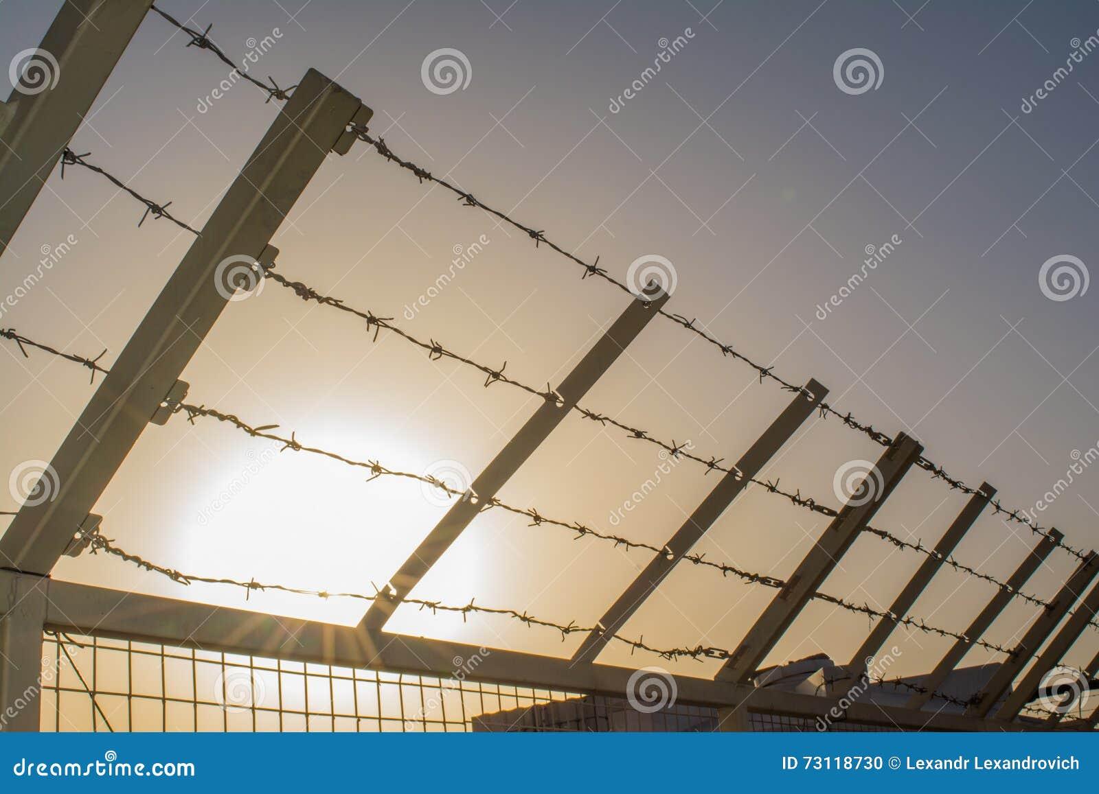 Gwożdżący drut na ogrodzeniu w więzieniu podczas zmierzchu czasu