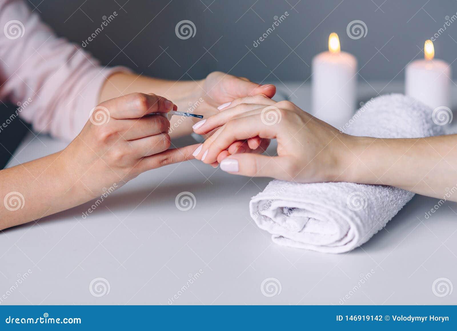 Gwo?dzia manicure I opieka Zbli?enie kobiety zdrowi naturalni gwo?dzie w pi?kno salonie Manicurzysta r?ka maluje klient?w gwo?dzi