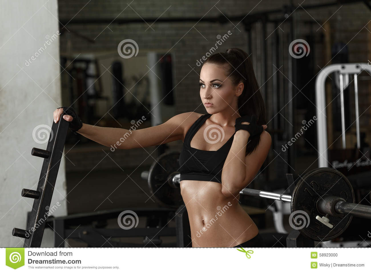 Gym. Beautiful woman posing sweaty after workout