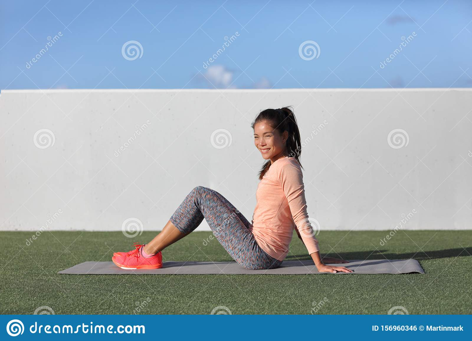 Gym fitness woman portrait relaxing on exercise mat in outdoor park grass. Happy Asian fit girl healthy active lifestyle ready for