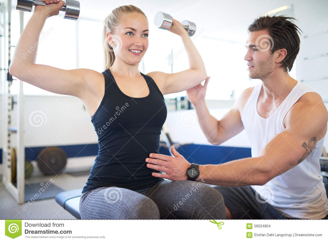 Gym Instructor Supporting Woman In Lifting Weights Stock Photo ...