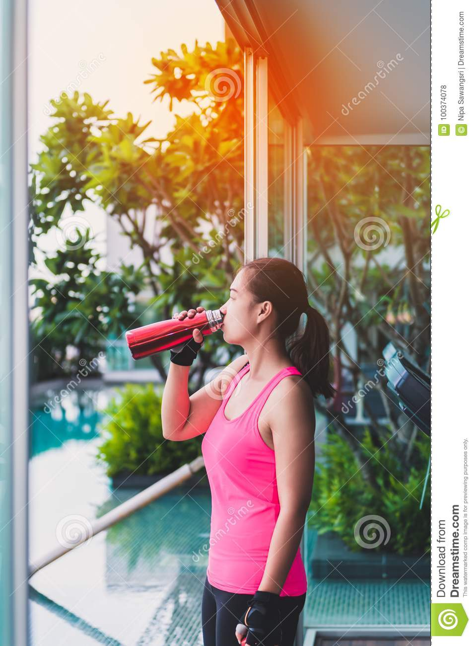 Gym woman working out drinking water at fitness center