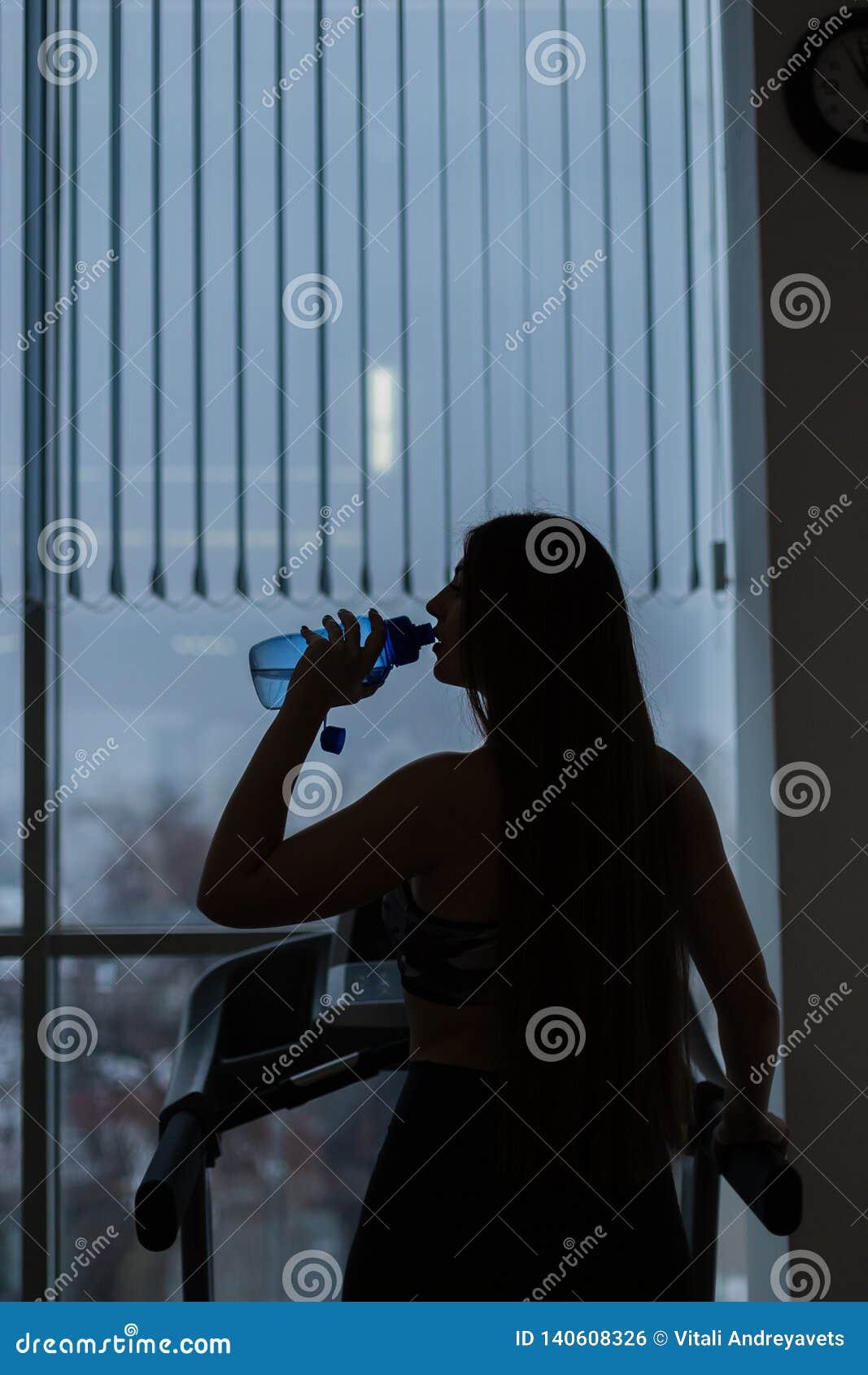Gymnastikfrau, die Trinkwasser lächelnde glückliche bereitstehende moonwalker Eignungmaschinen ausarbeitet Junges Misch des schön