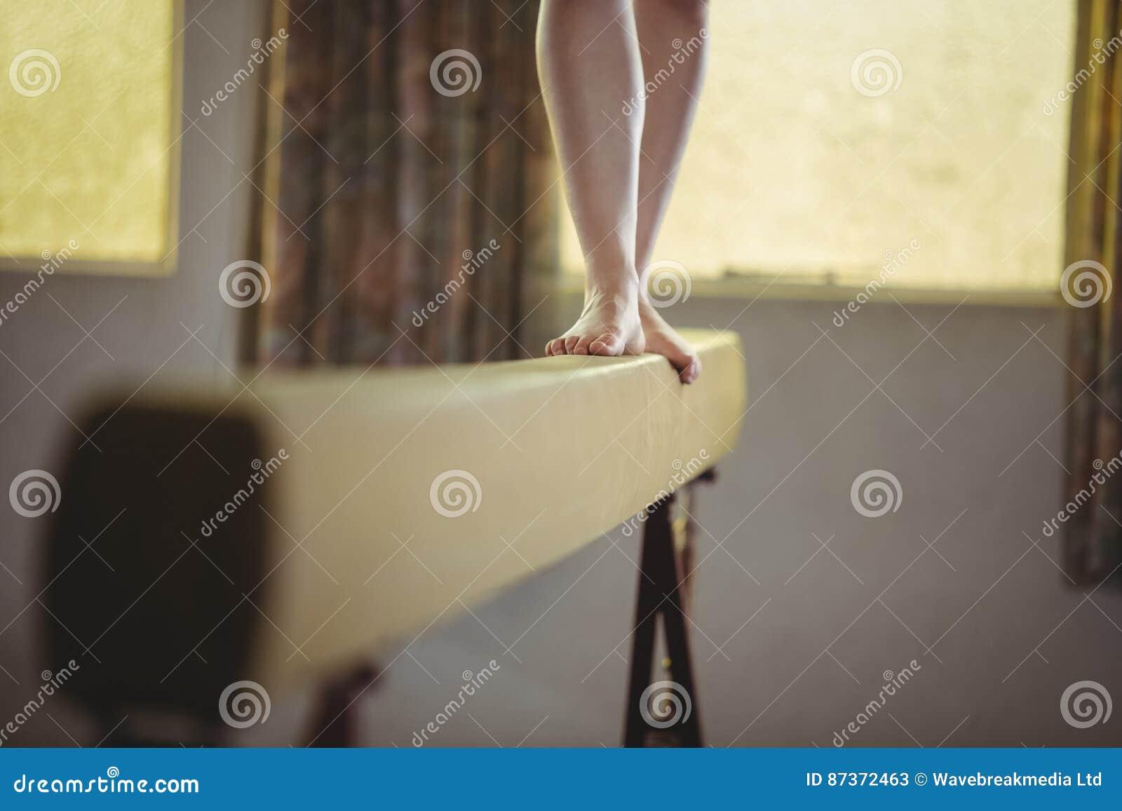 Gymnastique de pratique de gymnaste féminin sur le faisceau d équilibre