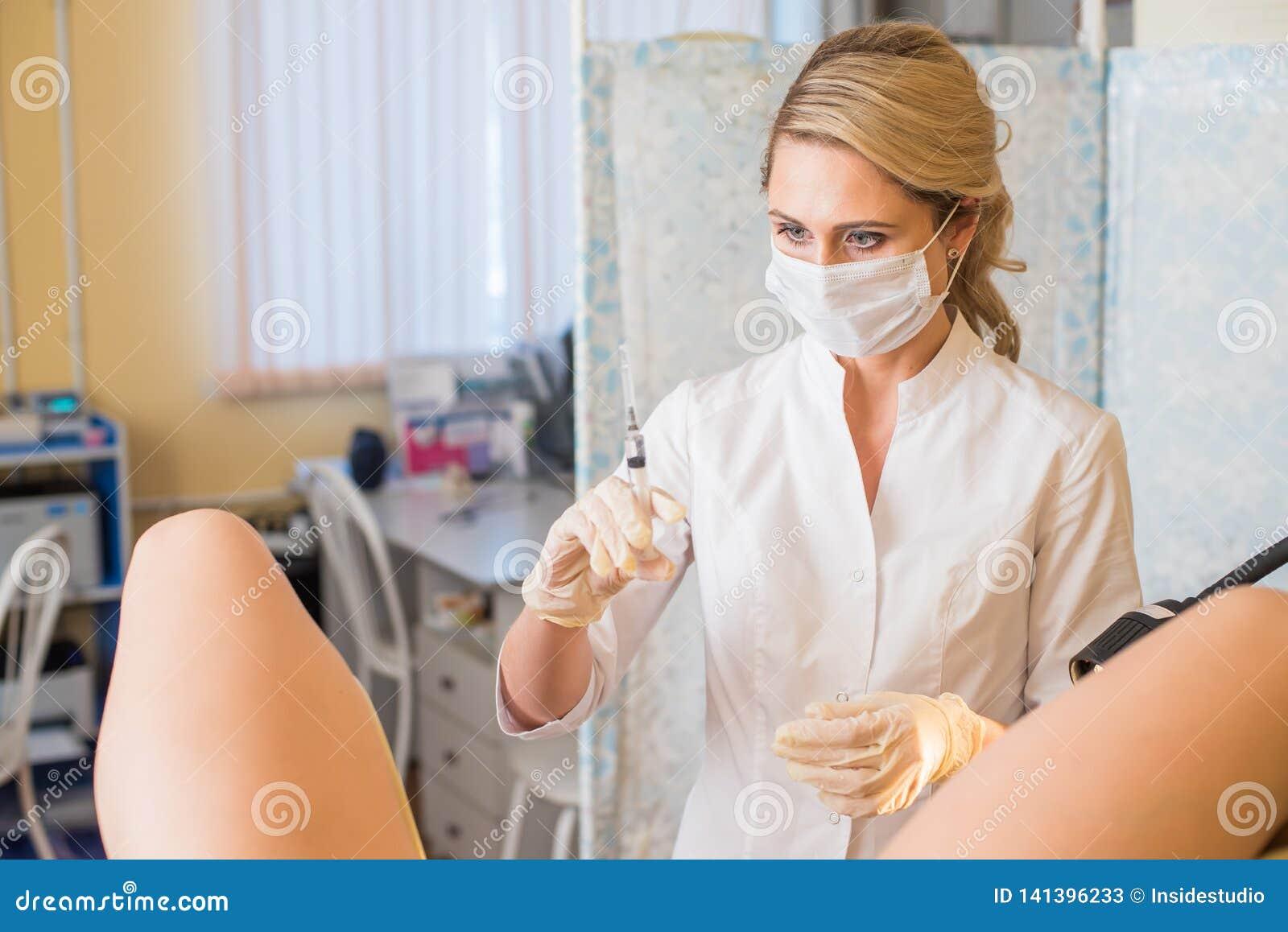 Gynekologen gör en injektion Den attraktiva doktorsgynekologen behandlar patienten
