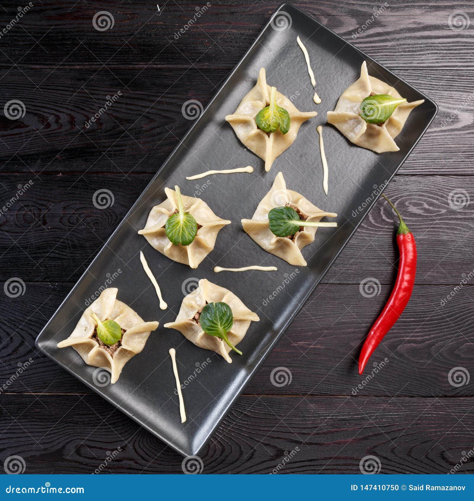 Gyoza用菠菜、乳清干酪和羊羔在一个黑色的盘子在黑暗的木背景