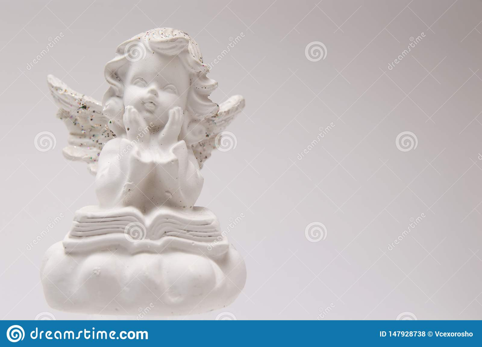 Gypsum white angel on a white background reading a book and thinking