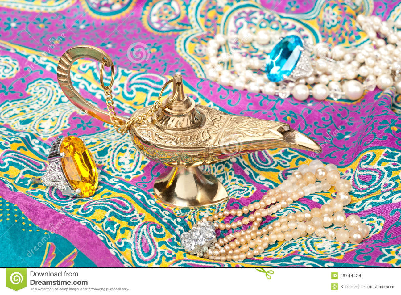 12270e6ced9 A magic oil lamp on top of gypsy clothing and surrounded by jewelry.